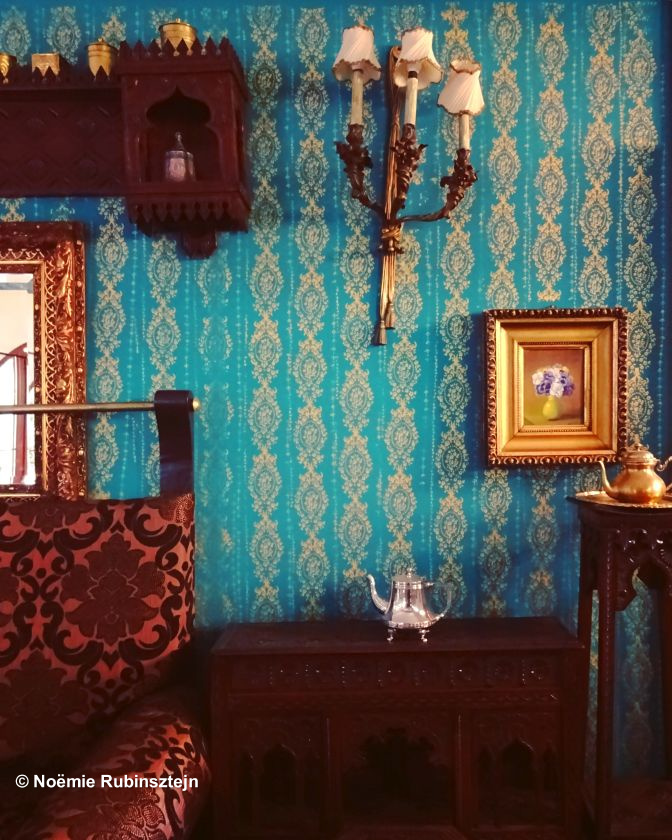 This photo was taken in Sarajevo and features part of the dining room of a hotel whose wallpaper was turquoise and whose sofa was velvet brown.