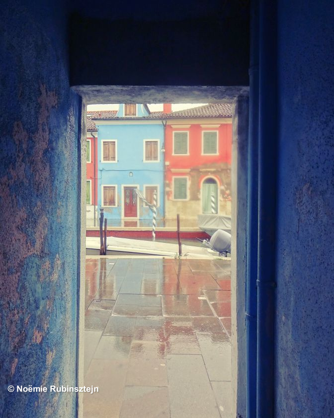 This photo was taken in Burano in Italy which is a fishermen's village where every house was painted in a different color so that sailors could recognize their house from afar. The day I visited the village was a very rainy one so I found a shelter in this beautiful passage.