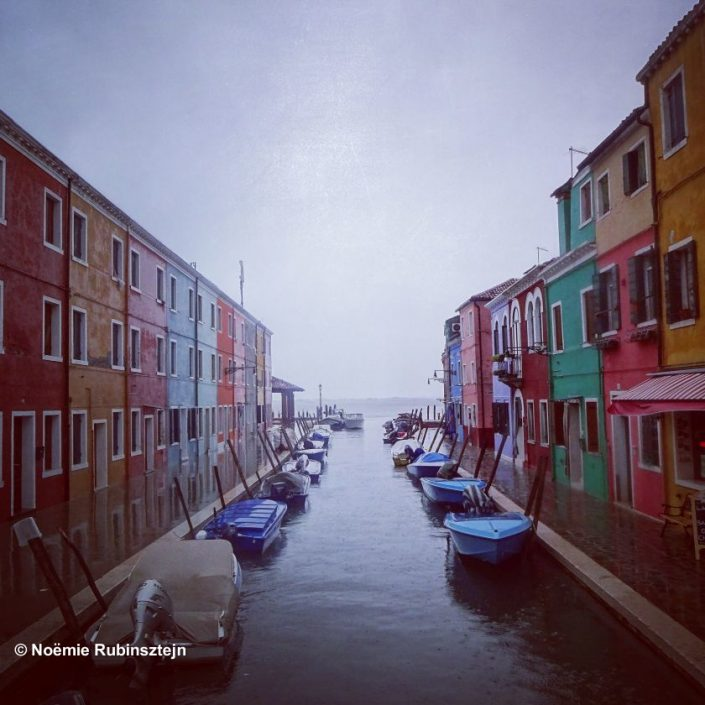 This photo was taken in Burano in Italy which is a fishermen's village where every house was painted in a different color so that sailors could recognize their house from afar. The day I visited the village was a very rainy one, hence the color of the sky.