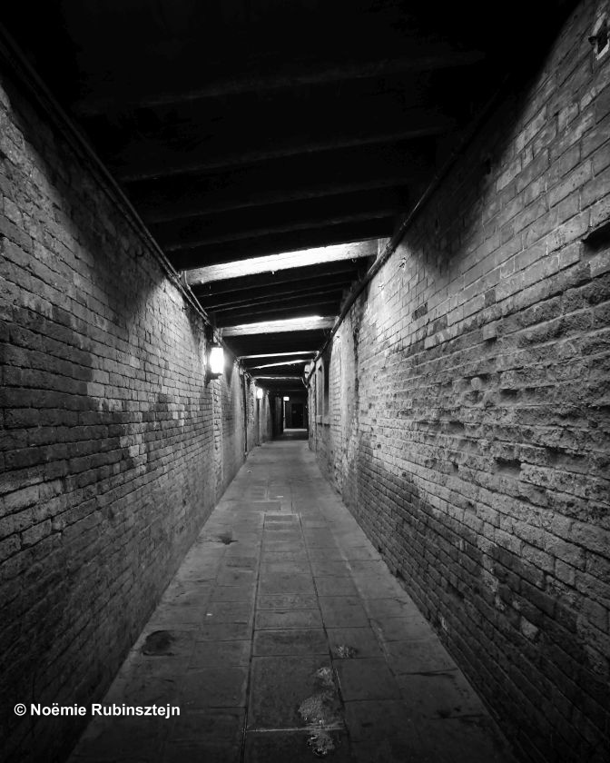 This photo was taken in Venice in the narrow and dark streets of the city.