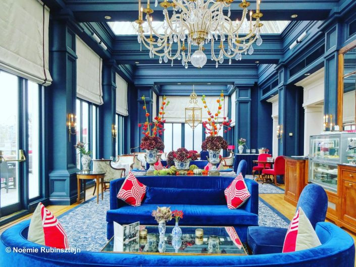 The photo was taken in the lobby in a hotel in Amsterdam and features a hall which is mainly blue; all the walls, pillars, sofas and carpets are blue.