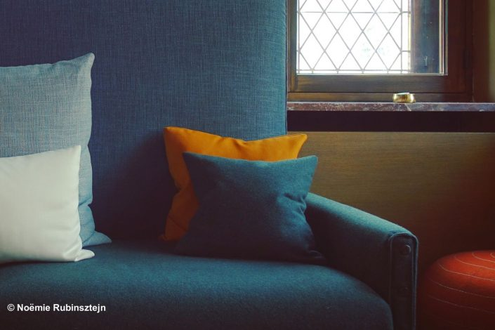 This photo was taken in the lobby of a hotel in Leuven, Belgium, and features half a light blue pillow, half a turquoise sofa, half a window and half a red poufe.