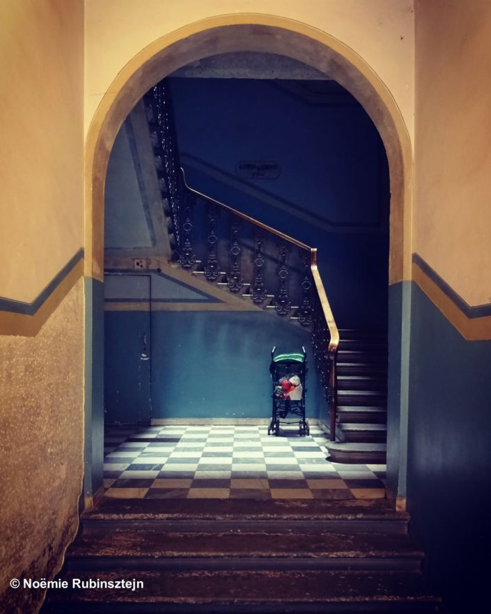 This photo was taken in the hallway of an old building in Florence and features a pram in the middle of a staircase. Light reflections are set on the pram which is surrounded by beautiful blue and yellow wallpaper colors.