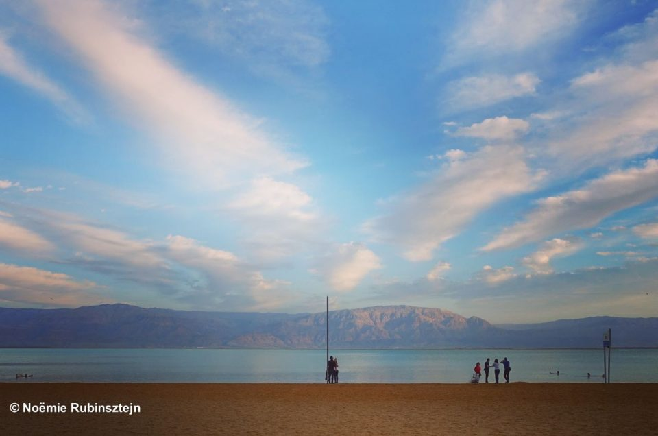 This photo was taken at the Dead Sea and features a beautiful sky overlooking the Dead Sea and its tourists.
