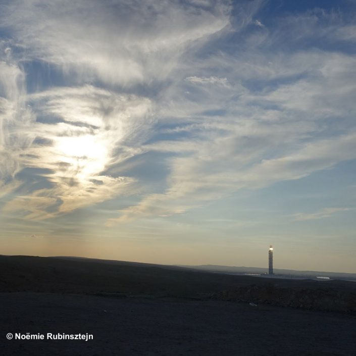This photo was taken in the Negev desert and features a cloudy sky which seems to reflect the light in a tower beyond.