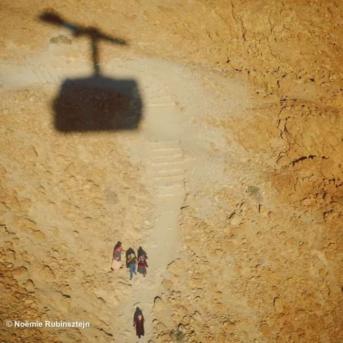 This photo was taken on Massada and features tourists mounting the Snake Road as above their head rises the shadow of the cableway.