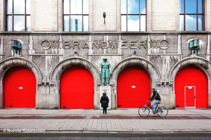 This photo was taken in Antwerp and features an old firefighter central, composed of giant firefighter statue surrounded by four red doors. A person is admiring the statue and another is biking in front of the building.
