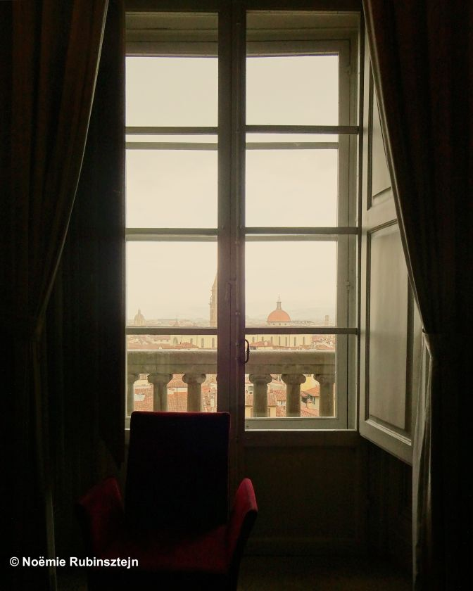 This photo was taken in Florence in a big house with a view on the city of Florence. A red sofa is standing in front of the window.