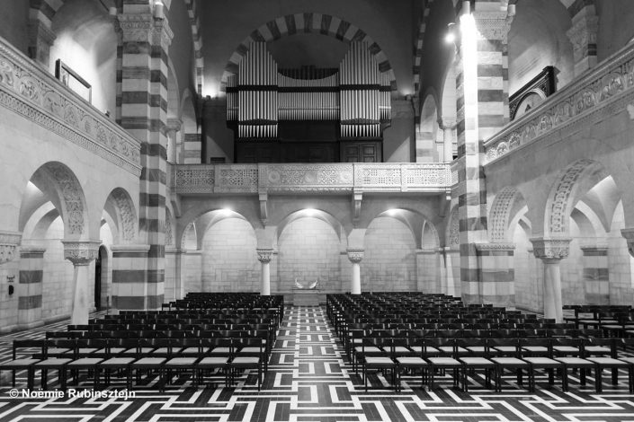 This photo was taken in a church in East Jerusalem featuring aligned chairs, pillars and a huge organ overseeing the whole. The photo is in black and white.