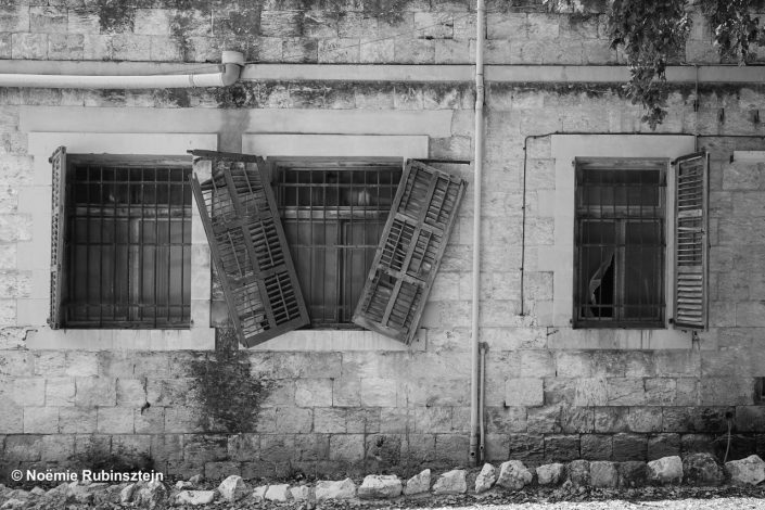 This photo was taken in Waldheim, Israel, and feature the façade of an old house and its broken windows. The photo is in black and white.