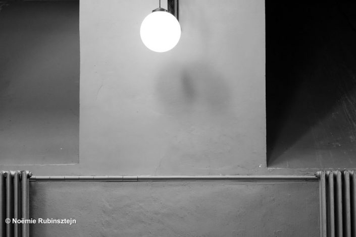 This photo was taken in Antwerp in one of the corridors of a restaurant and features a lamp hanging in the middle of two radiators. The picture is in black and white