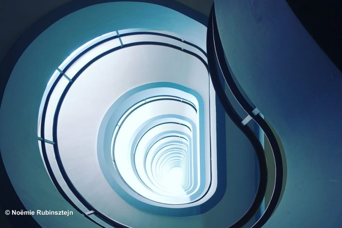 This photo was taken in Antwerp in the staircase of a big tower in Antwerp, Belgium. The stairs are in white marble, the walls in light blue and the floor was made out of black and white cubic marble tiles.