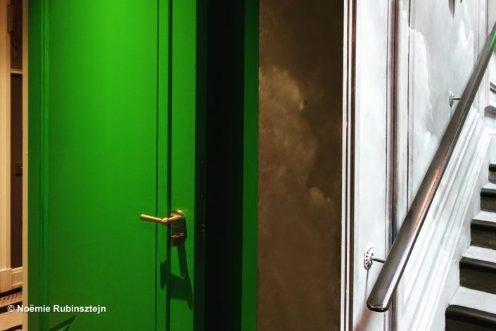This photo was taken in Paris and features the encounter in a hotel between a white staircase and a green door.