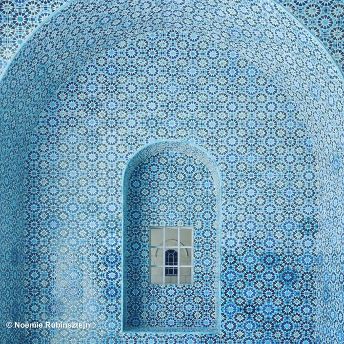 The photo was taken in East Jerusalem at the Rockefeller Museum and features a wall and a window in its middle composed of various different blue tiles.