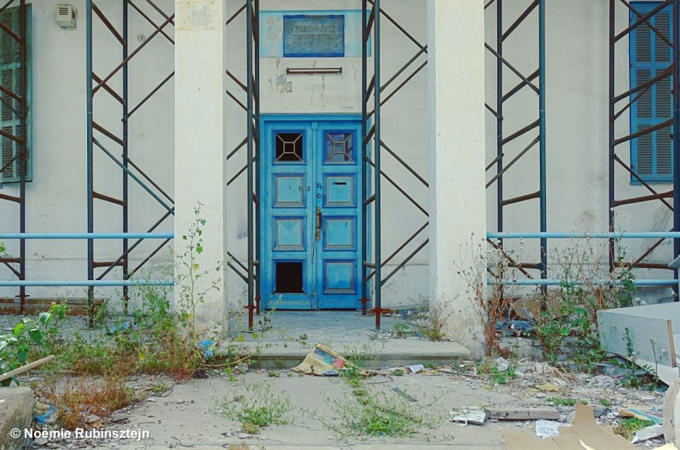This photo was take in Tel Aviv and features the entrance to a synagogue which is being restored. The door and the fences are both in blue tints.