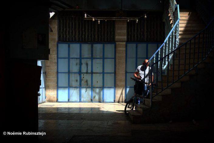 This photo was taken in a tiny passage in East Jerusalem and features a corner overflown by shadows and lights on a man and his bicycle and the surrounding stairs. The many color of the photo is blue.