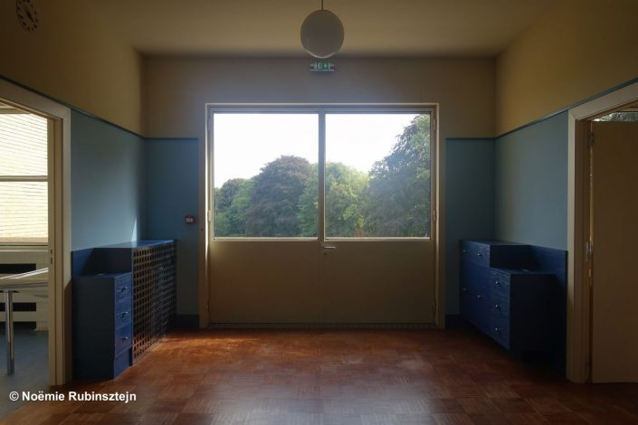 This picture was taken in Croix, France and features one of the rooms of an Art Deco villa. There is a window with a view on the trees of the garden, blue cupboards, a small round chandelier, a wooden floor and two open doors leading to other rooms.