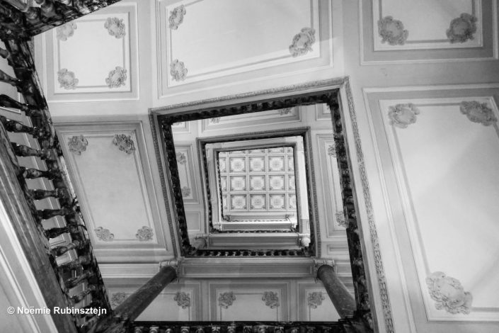 This photo was taken in Rome at the staircase of a hotel. The picture is in black and white and features pillars, stairs and the roof of the staircase.