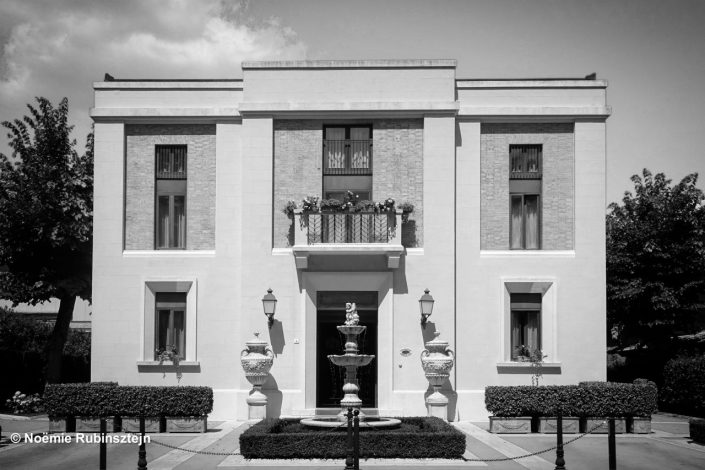 This photo was taken in Tuscany and features the facade of a hotel in black and white. Everything about the hotel is symmetric.