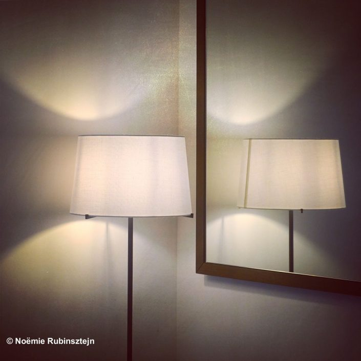 This photo was taken in Antwerp in a hotel and features a chandelier in front of a mirror admiring its reflection.