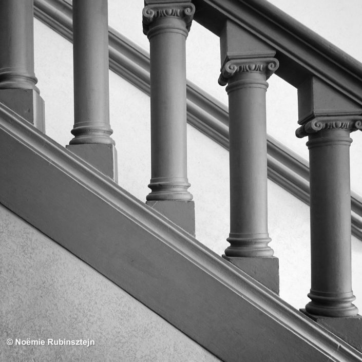 This photo was taken in Florence in a big house with a closeup on a staircase in black and white.