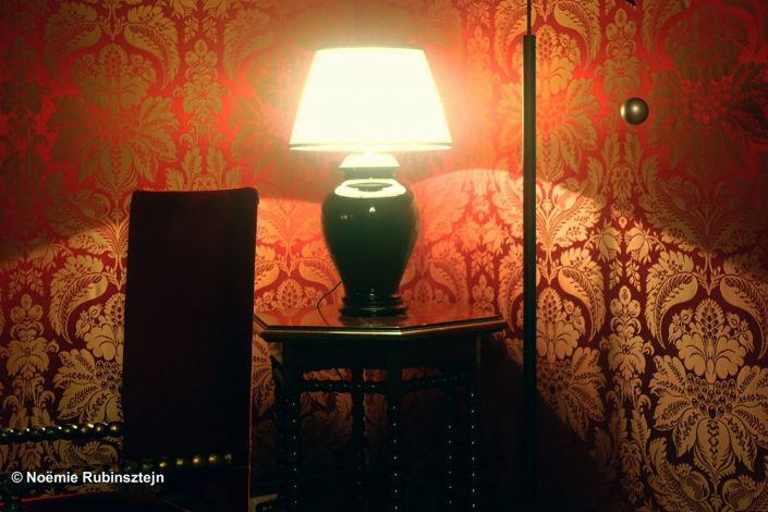 This photo was taken in Rome and features a closeup on a chandelier, an old chair and table and a ball, surrounded by red wallpaper.