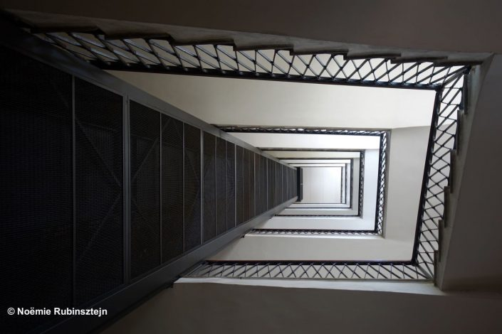 This photo was taken in Rome in a building and features its staircase and elevator.