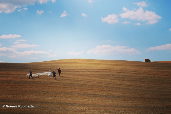 This photo was taken in Tuscany and features a bridal photo shoot in the middle of the Tuscan fields.