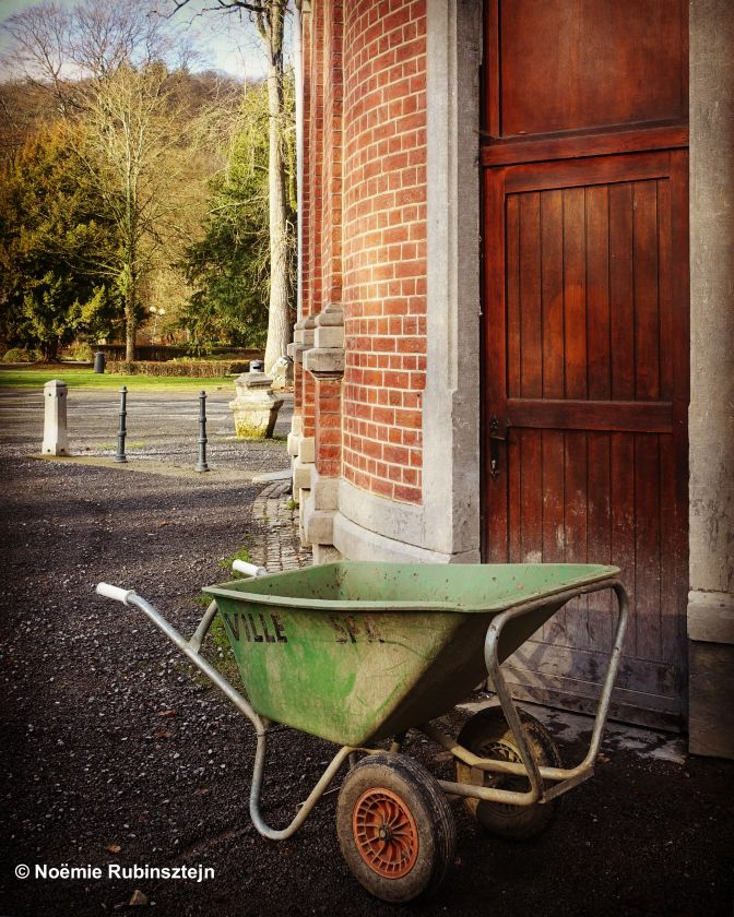 This photo was taken in Spa and features a green wheelbarrow in the corner, near the entrance to the city's therms.