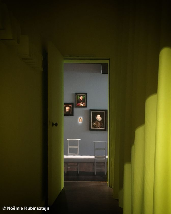 This photo was taken in Antwerp, Belgium, and features a corridor leading to artistic paintings from the Renaissance. The corridor was painted in yellow.
